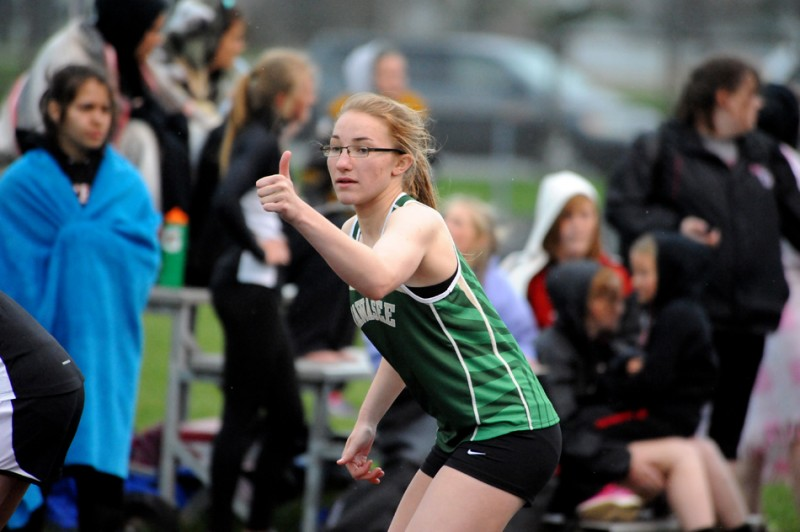 Wawasee's Bridgette Yoder directs her teammate Skylar Janda to the line in the 4x400 relay race.