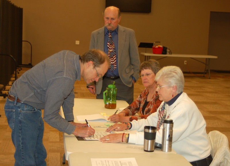 At Van Buren Precinct 3, Nathan Warstler signs in early this afternoon to vote. Morning and lunchtime voting was light but steady, Precinct Judge Allen Brunjes said.  From left are Warstler, Brunjes and poll workers Kay Tusing and Mary Duncan. (Photo by Jodi Magallanes)