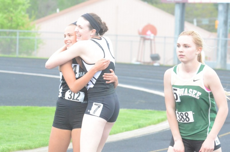 Warsaw senior Ann Harvuot gives teammate Mariah Harter a big hug after they placed 1-2 in the 100 Tuesday night at the NLC Meet.