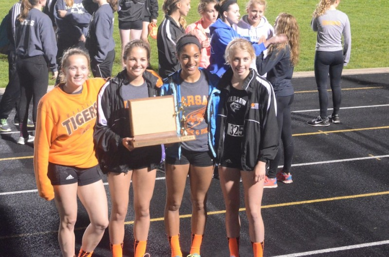 The Warsaw 4 X 400 relay team proudly shows off the NLC Meet trophy Tuesday night.
