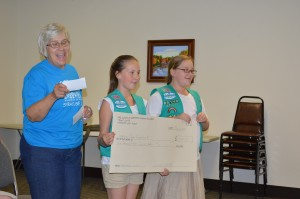 Girl Scout Leader Barb Grumme, left Girl Scout Sophia Grumme and Girl Scout Aly Kirkpatrick, all of Troop No. 00148 presented the Syracuse Park Board with a check for $1,500 to purchase a swing for handicapped individuals to use. The girls requested approval from the park board to proceed with fundraising for the project, which the park board gave. Not pictured are Tina Walton, assistant leader, and Andrea Chaney, community liaison for the troop.