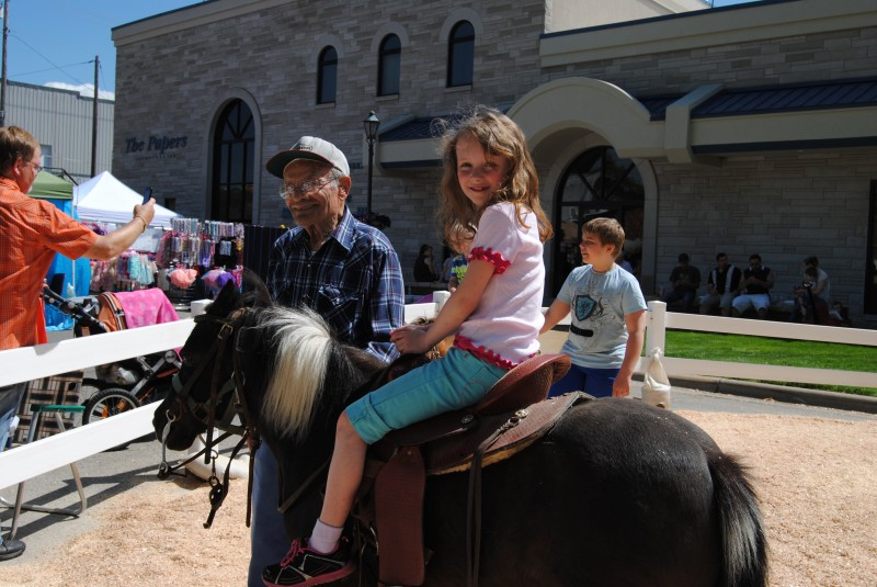 Cap Beer helps Isabel Schwartz, 7, on the pony ride at today's Milford Fest.