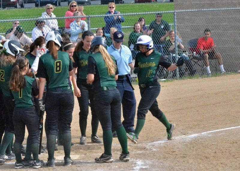 Danielle Gunkel is greeted at home plate by her teammates after her home run in the bottom of the first inning.