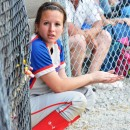 Hanna Yohe sits at the entrance of the dugout during her team's at-bat on Tuesday night.