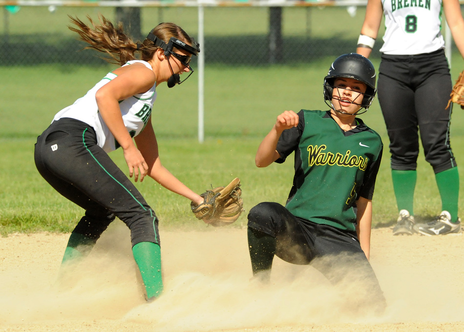 Wawasee's Cristina DeLaFuente slides in under the tag attempt of Bremen's Brooke Fitch after doubling in the first inning Friday night. Bremen would win the game 6-3. (Photos by Mike Deak)