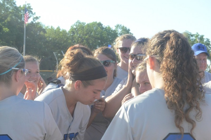 An emotional Mallorie Jennings is surrounded by her teammates Tuesday night. Jennings pitched the Trojans to the first regional championship in program history.