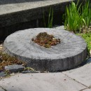 This stepping stone used at the home of Tom Knopp in Syracuse is an old millstone formerly used in Crosson Mill in Syracuse.
