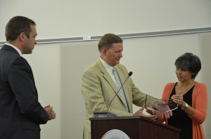 Dr. Craig Hintz (center) is awarded a district award by Dr. David Hoffert (left) and Board President Jennifer Tandy.  (Photo by Alyssa Richardson)