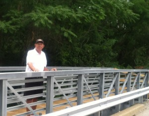 Bill Musser of the Syracuse Town Council stands on the new bridge over Harkless Drive.
