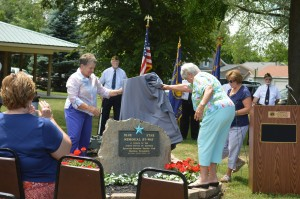 After months of work, the Syracuse-Wawasee had a Blue Star Memorial placed in Veteran's Memorial at Crosson Mill Park Sunday afternoon. Shown are Carol Koble, left, and Jo Butler unveiling the marker which has been placed by the cannon in the park. Approximately 50 people attended the dedication ceremony. (Photo by Lauren Zeugner)