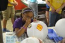 Molly Greer focuses on her work as she paints superhero logos on her lantern during arts and crafts at Deaf Camp.