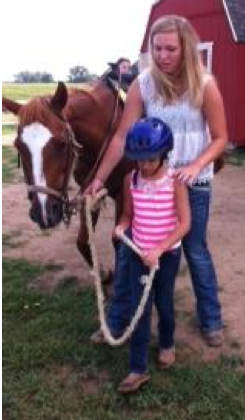 Sydney Susaraba assists Kyla Cook to lead the horse to the corral at Magical Meadows. (Photo provided)