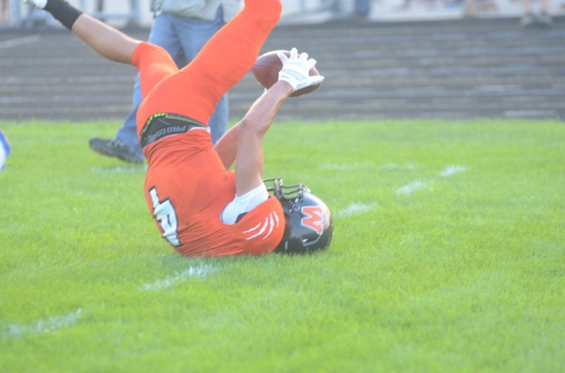Warsaw's Riley Rhoades lands upside down trying to make a catch Friday night.