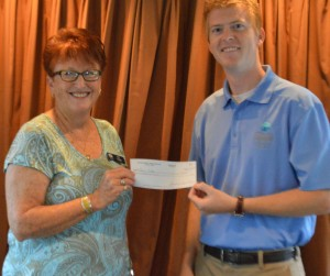Kay Young, president of Wawasee Property Owners Association, present Dr. Nate Bosch, Center for Lakes and Streams, a check to support an aquarium at Syracuse Elementary. (Photo by Deb Patterson)