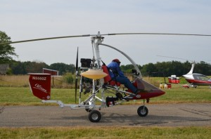 A FINAL CHECK — Christine Toeves gives a final tug to her safety harness before gliding onto the runway and into the sky in her home-built rotorcraft. In the background is a fully assembled kit aircraft. (Photo by Keith Knepp)