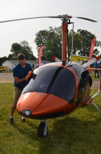 SLEEK AND BEAUTIFUL— Dan Saunders polishes a factory-assembled gyrocraft that he was offering for sale during last week's Popular Rotorcraft Association convention in Mentone. (Photo by Keith Knepp)