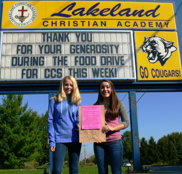 Lakeland Christian Academy students Baylee Wiley (left) and Veronica Flores (right).  They are holding one of the 5,000 bags donated by Owens Supermarket that the LCA students will be distributing today.