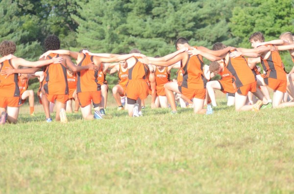 The Warsaw boys cross country team huddles up prior to the start Tuesday.