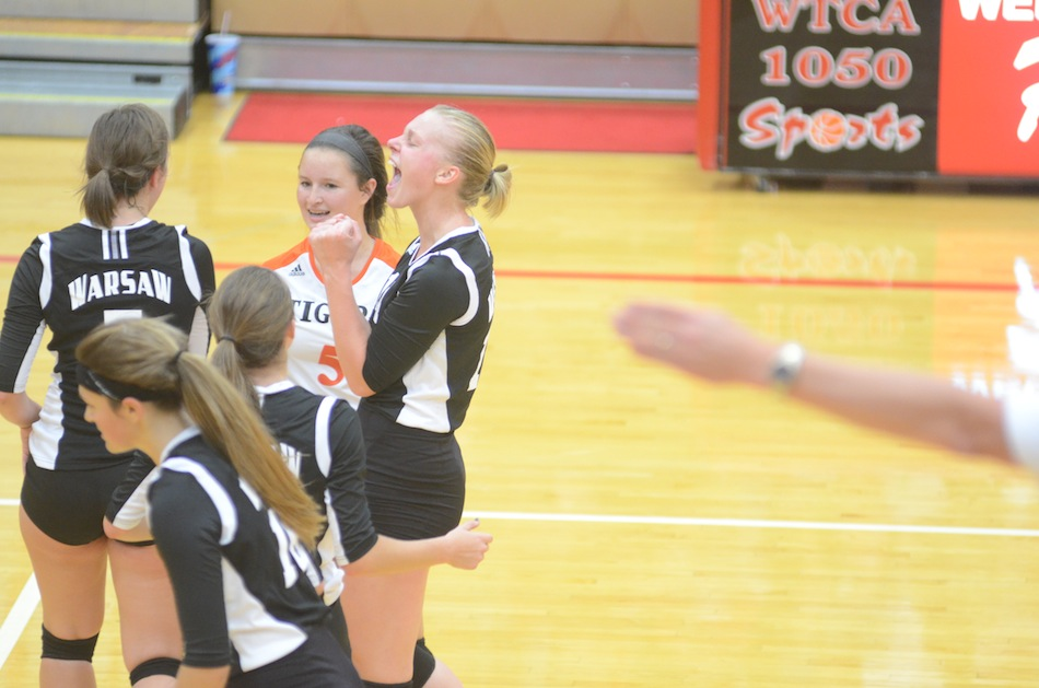 A fired-up Katie Voelz celebrates for Warsaw during a key NLC volleyball victory  at Plymouth Thursday night.