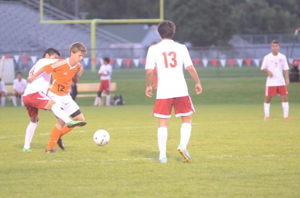 Warsaw's Brad Ocock protects the ball versus host Goshen Thursday night. The No. 15 Redskins won 2-1.