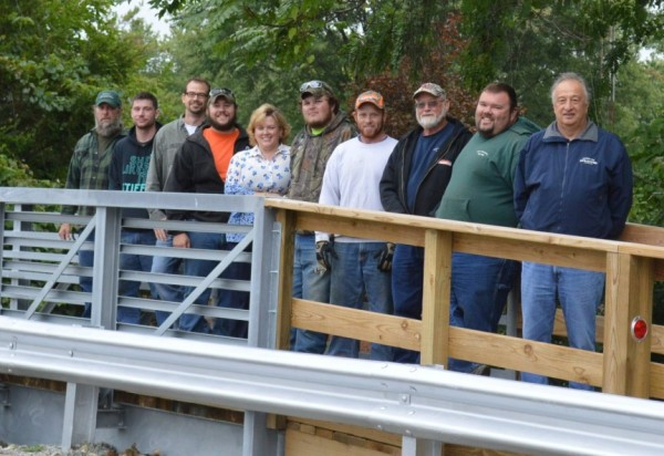"""Shown are members of the Syracuse Street Department who worked on constructing the pedestrian bridge on Harkless Drive. Construction was started in May and completed in mid-July. From left are Paul Hoffman, street foreman; David Miller, Jeremy Sponseller, public works director; Zach Goodyear, Holly Swoverland, representing K-21 Foundation; Jared Hoover, Seth Hall, Ken Plikerd, John """"Tiny"""" Reynolds and Town Manager Henry DeJulia."""