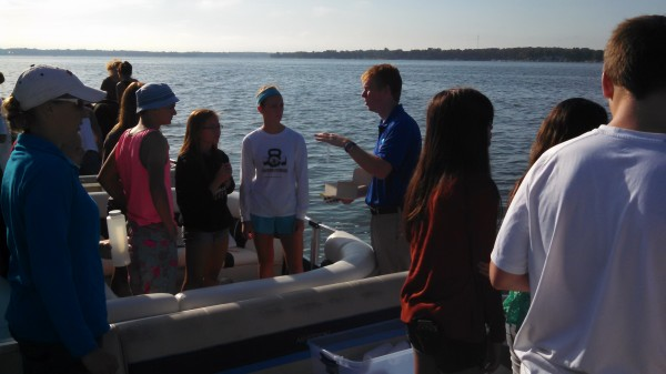 Dr. Nate Bosch, far right, director of the Center for Lakes and Streams at Grace College, addresses Wawasee High School honors biology students, from left, Cayden Wegener, Adrienne Gill and Kabrea Rostochak at Lake Wawasee.