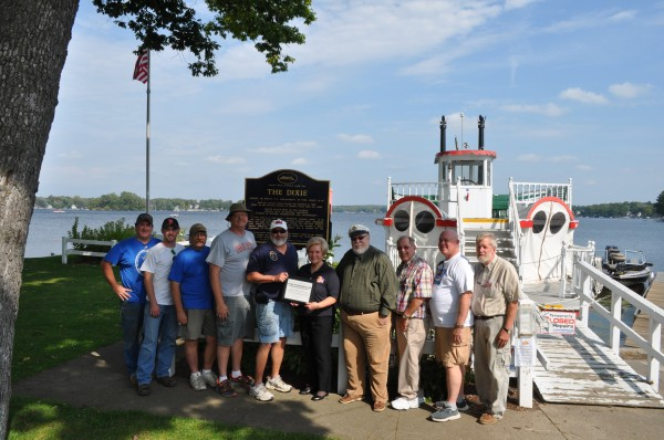 Officers of the Antique Outboard Motor Club with a certificate of appreciation for support of Dixie Sternwheeler Inc. North Webster. From the left are Jay Walls, JJ Walls, Mark Majcher, Richard White and Rick Eichrodt, all of the motor club; and Karilyn Metcalf, Bob Barnes, Jim Tranter, Russ Boucher and Dave Tranter representing theDixie. (Photo provided)