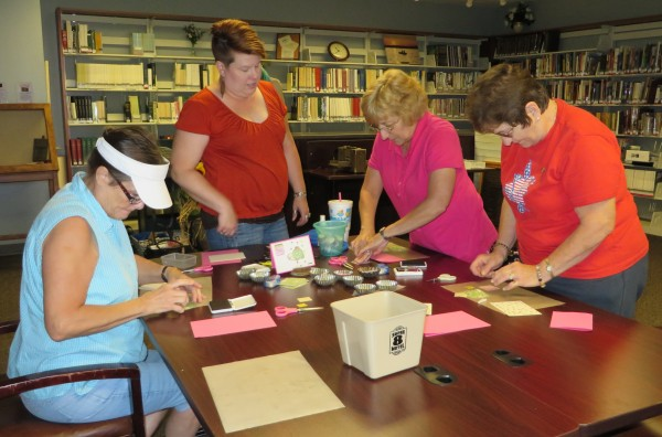 Instructor Hope Beezley (second from left) shows Pam Pollard, Sherrie Sigler and Jeri Felts how to make their own greeting cards during the Make & Take Card Class held the first Thursday each month at the library. (Photo provided)