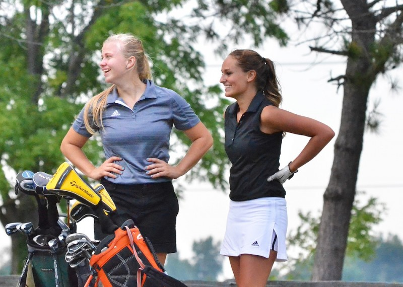 Wawasee's Kylee Rostochak (left) and Warsaw's Kristen Watson (right) share a laugh after teeing off on number seven. (Photos by Nick Goralczyk)
