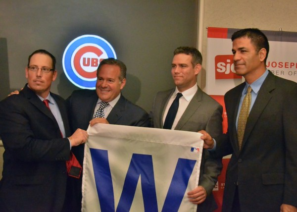 From left to right South Bend Cubs President Joe Hart, South Bend Cubs owner Andrew Berlin, Chicago Cubs President Theo Epstein and Chicago Cubs Director of Player Development Jason McLeod all pose with a 'W' flag following the press conference held at the St. Joseph's County Commerce Center. (Photos by Nick Goralczyk)