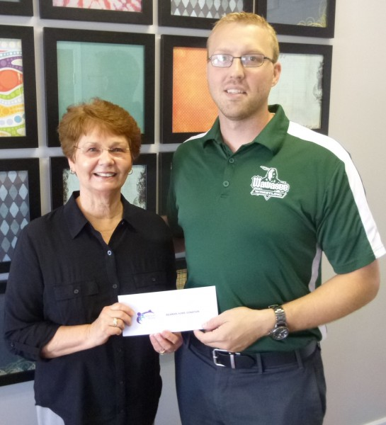 Sue Creighton, Beaman Home Capital Campaign Chair, accepts a $950 check from Dr. Erick Leffler, president of the Syracuse-Wawasee Rotary Club. (Photo provided)