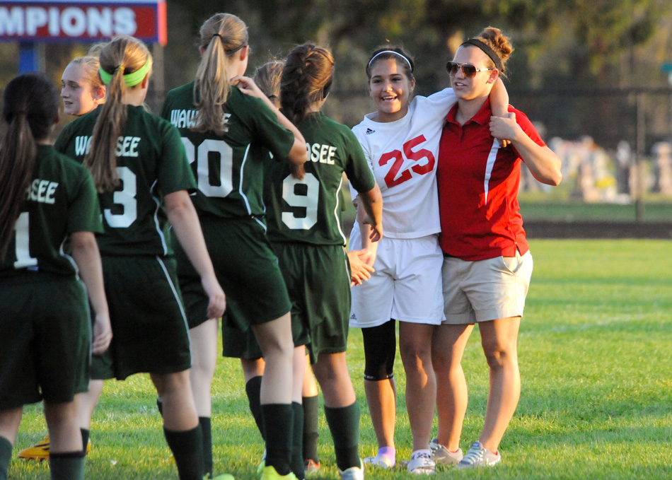 Whitko's Leighandra Goodman (25) is assisted by coach Christina Baughman while Wawasee players greet her following the match. Goodman injured her ankle in the second half and did not return.