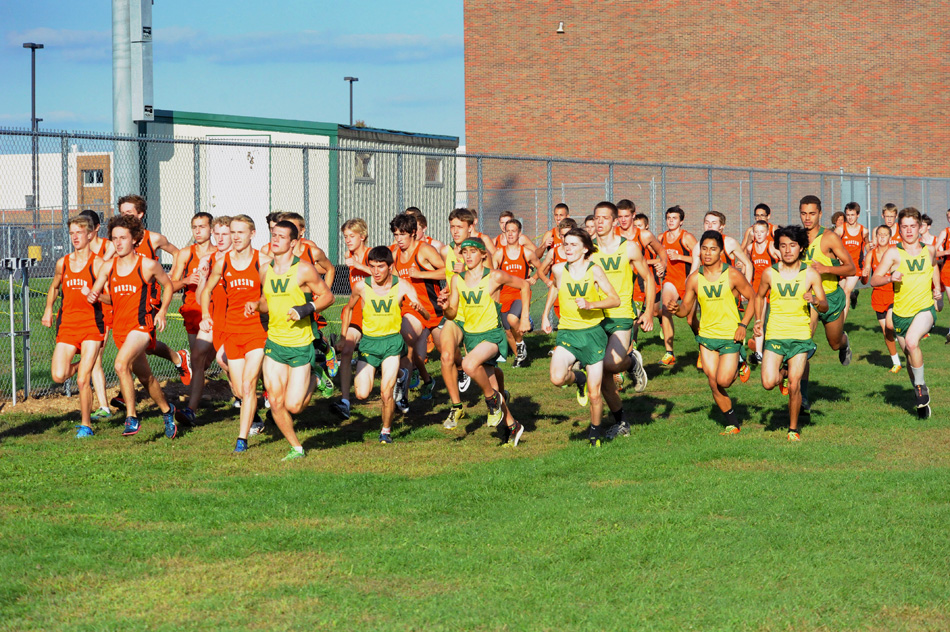 Members of the Warsaw and Wawasee boys cross country teams make a break at the start of the race Tuesday night at Wawasee.