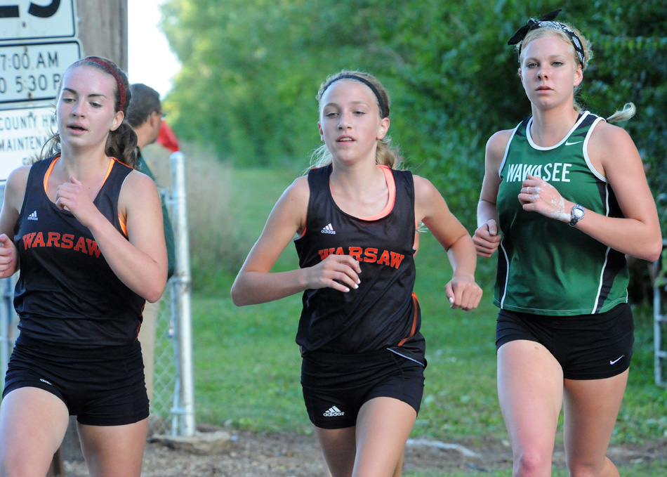 Warsaw's Claire Kehler and Mia Beckham run with Wawasee's Courtney Linnemeier.