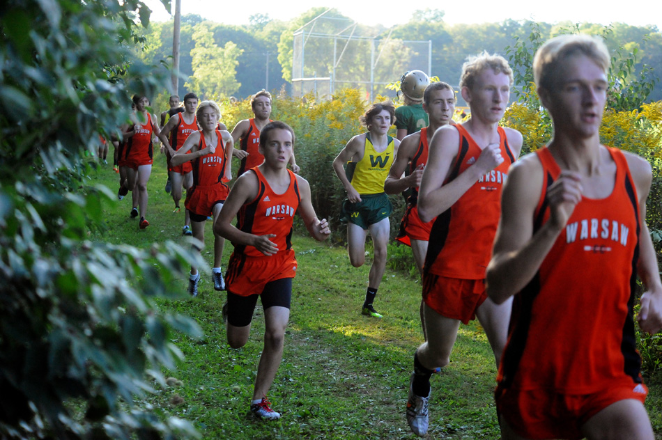 Members of the Warsaw and Wawasee cross country teams stampede up the straightaway at Wawasee.