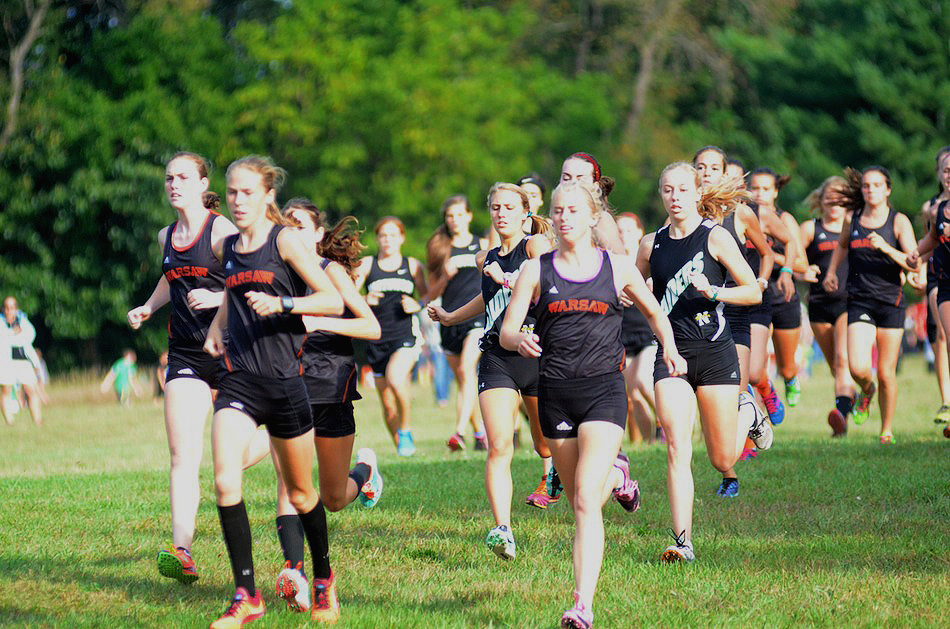 The Warsaw girls cross country team leads the pack at the start Tuesday night.