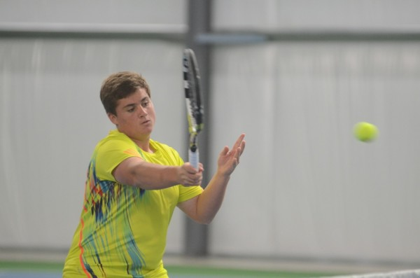 Christopher Herendeen hits a shot at the net for the Tigers in No. 1 doubles play.