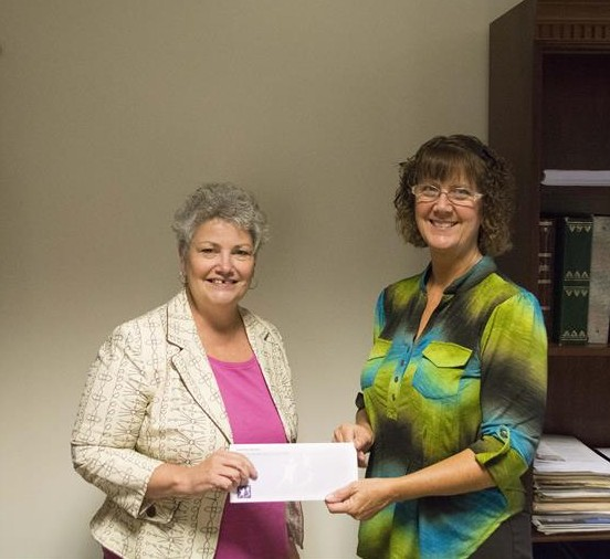 Pictured in the photo from left to right are Trina Hoy, Community Development Director for Big Brothers Big Sisters in Kosciusko County, accepting a check from Cindy Hepler, Board Member The Dr. Dane & Mary Louise Miller Foundation.
