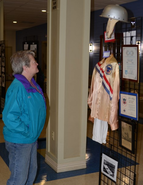 Sherry Carey takes a look at Steve Lewis' uniform and other memorabilia from his Soapbox Derby participation. (Photo by Deb Patterson)