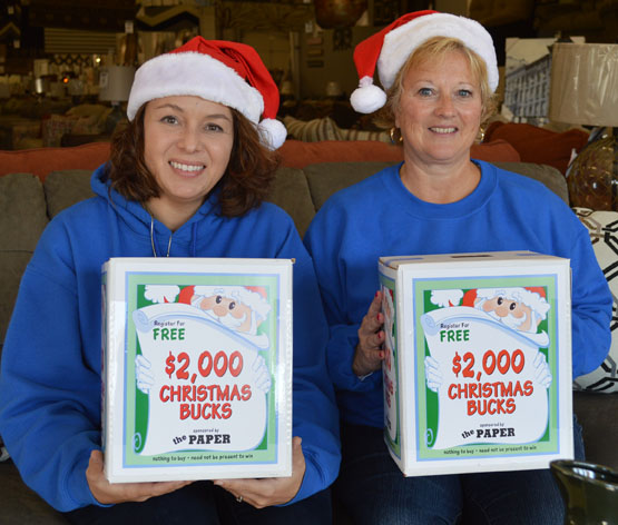 Heather Batalis, left, and Sonia DeGaetano of Furniture Factory Outlet in Warsaw are in the Christmas spirit to help promote Christmas Bucks. (Photo by Tim Ashley)