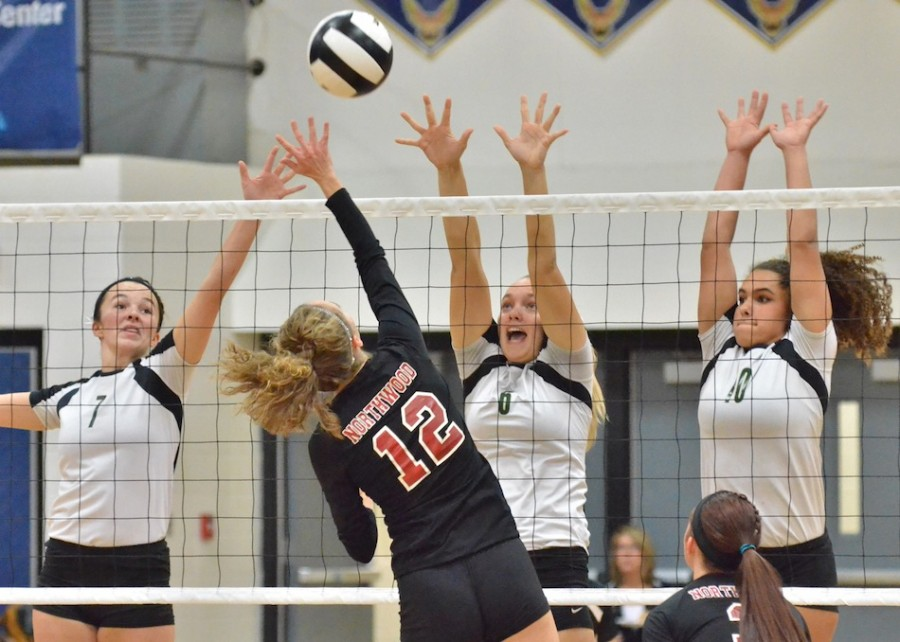 Alli Ousley (7), Meghan Fretz (6) and Seaquinn Bright (10) all go up for a block during the first game of Saturday's match.