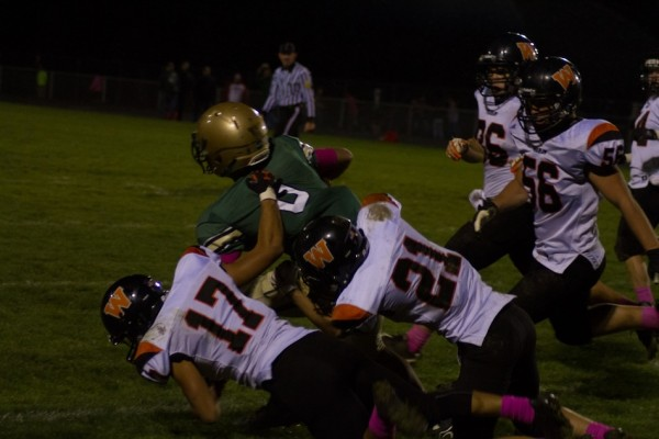 Landan Perry (No. 17) and Brett Fancil (No. 21)  of Warsaw make a stop for the Tigers.