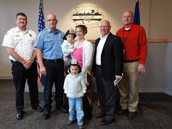 Troy Knefelkamp was sworn in Monday morning as the newest firefighter with the Warsaw-Wayne Fire Territory. Shown in front is his son Leighton. In back are Chief Michael Brubaker, Knefelkamp, Nicole Leighton holding Maxton Knefelkamp, Charles Smith and Jeff Grose, board of public works members. (Photo by Deb Patterson)