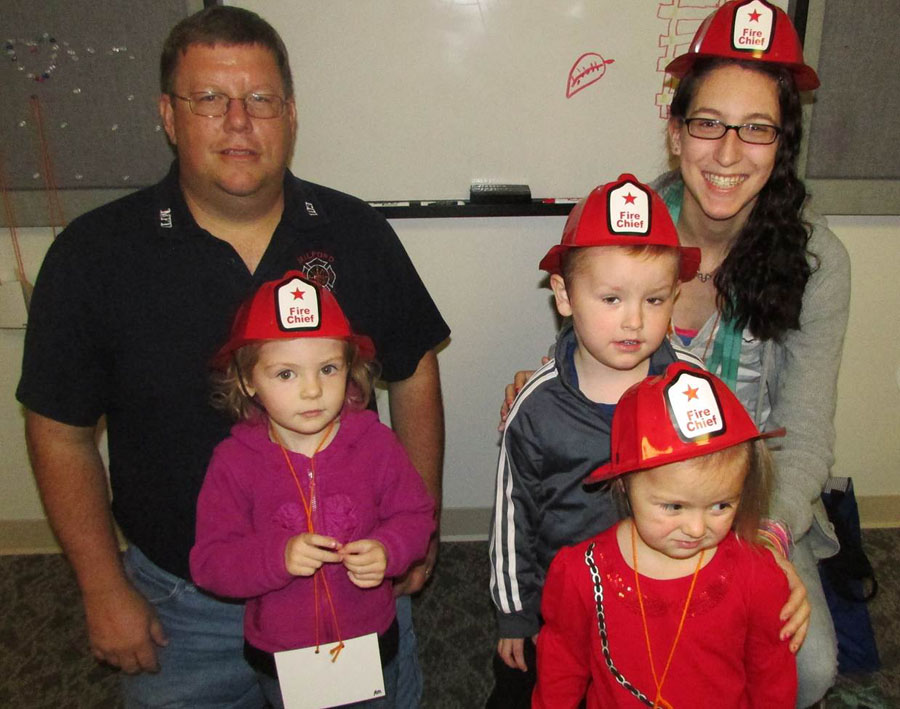 Celebrating Fire Prevention Week with volunteer fireman Brian Haines. Back Left to Right: Brian Haines and Malea Johnson. Middle Left to Right: Madeline Linville and Lukas Suranyi. In front: Lylah Young