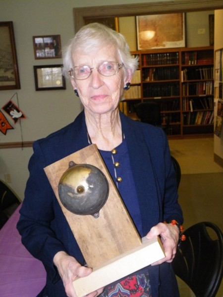 """County Historian Fern Eddy Schultz holding the """"haunted"""" doorbell from the Andrew- Zimmerman house."""