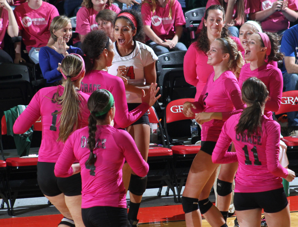 Grace College's women's volleyball team celebrates a point Friday night against Huntington.