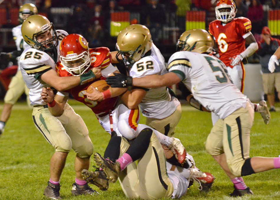 Wawasee defenders Nathan Katzer (25), Maclain Herr (52) and Stephen Possell (58) converge on Elkhart Memorial's Andrew Goodman during Wawasee's 20-7 win at Memorial Friday night. (Photo provided)