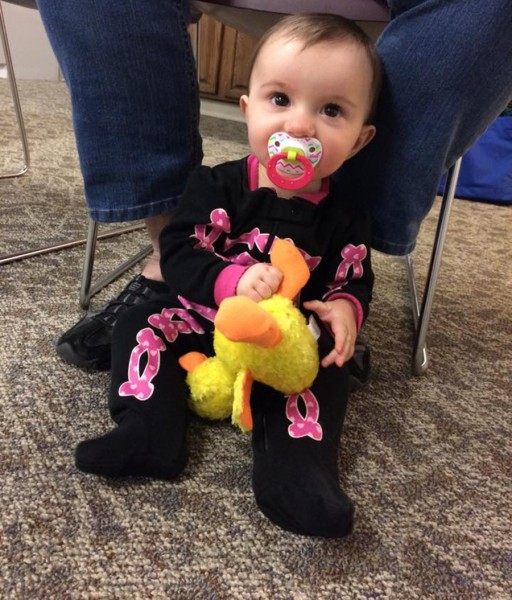 Abby Bradley plays with a stuffed animal duck at Duck Lapsit.