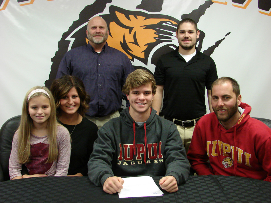 Warsaw Community High School senior Jayden Parrett, center, has signed a national letter of intent to continue his swim career at IUPUI. Seated with Jayden are Macelyn Marcuccilli, Jena Marcuccilli, Jayden Parrett and Michael Marcuccilli. In the back row are WCHS athletic director Dave Anson and WCHS boys swim coach Anthony DeBrota. (Photo provided by WCHS athletics)