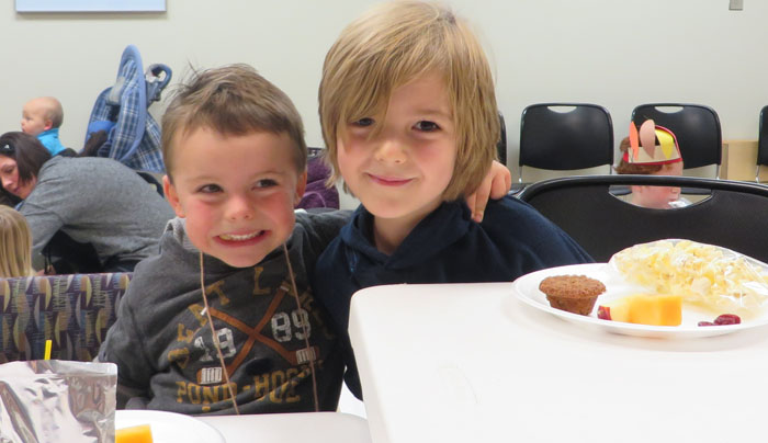 Everett Guy and Landon Russell share a finger food Thanksgiving feast during the final session of fall Preschool Story Time. (Photo Provided)